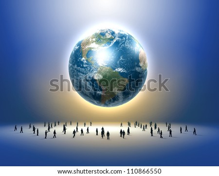 Planet earth and tiny human figures standing below it - stock photo