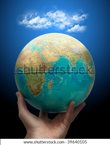 Planet earth holding in hand with clouds above.Weather concept