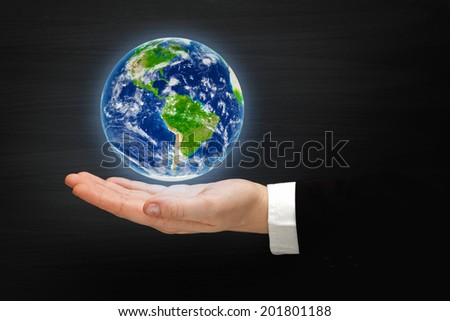 Planet Earth on a hand. Elements of this image furnished by NASA