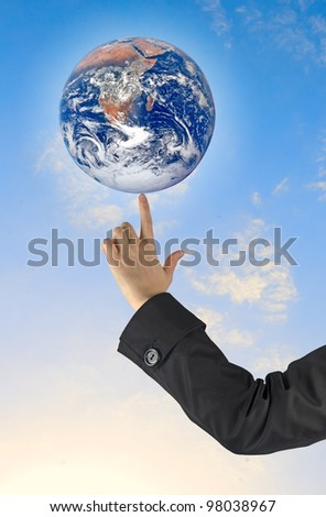 Planet earth on finger.Elements of this image furnished by NASA