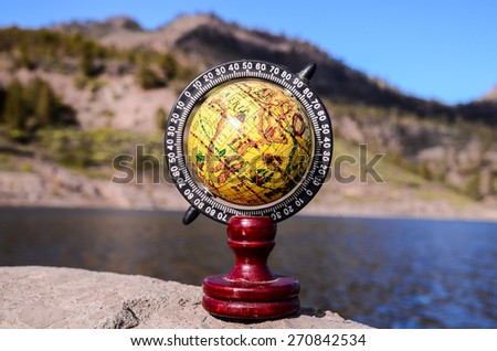 Planet Globe Earth on the Rock near the Water - stock photo