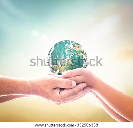 Planet in father and son hands on blurred beautiful nature background. Eco Friendly Environment Human Rights Day World Religion Cancer CSR Earth Sick concept. Elements of this image furnished by NASA - stock photo
