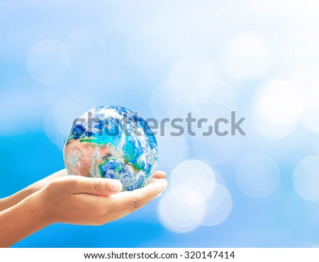 Planet in human hands on beautiful blue bokeh nature background. Environment, World Science Day for Peace and Development, World Autism Awareness Day concept. Elements of this image furnished by NASA. - stock photo
