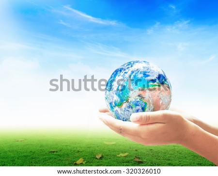 Planet in human hands on beautiful nature background. environment concept. World Mental Health Day concept. Elements of this image furnished by NASA.  - stock photo
