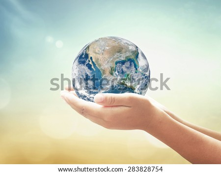 Planet in human hands on blurred beautiful nature background. Investment, Ecology, World Environment Day, CSR, Mission, Ecosystem, Search concept. Elements of this image furnished by NASA. - stock photo
