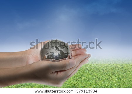 Planet in human hands on nature background. environment concept. Elements of this image furnished by NASA.