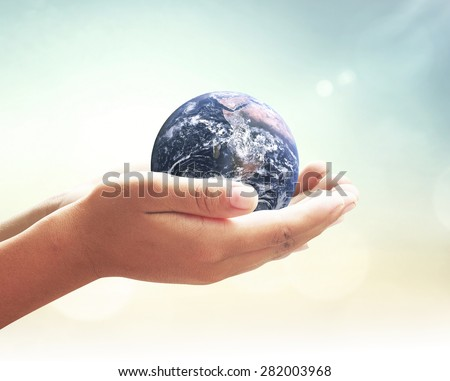 Planet in human hands on nature background. Solidarity World Unity Hour Earth Day CSR Spring Time Languages Justice Support Life Kid Trust Globe Map Idea. Elements of this image furnished by NASA. - stock photo