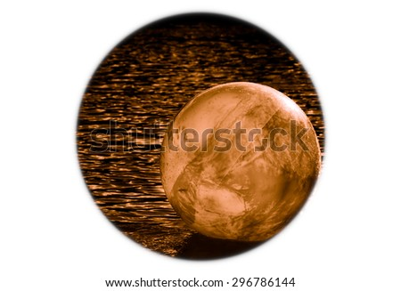 planet like orb floating or rolling around on a watery surface  - stock photo