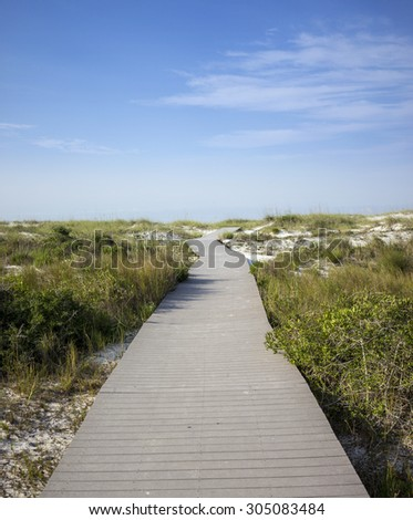 Plank boardwalk through wetlands leading to beach in Pensacola, Florida.