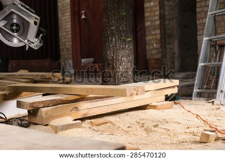 Planks of Wood Surrounded by Saw Dust at Construction Site of New Home - stock photo