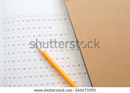 planner and money on wooden table - stock photo