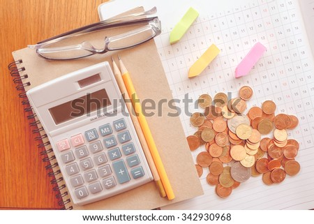 planner and money on wooden table with vintage style