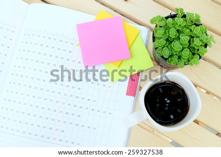 planner book and office tools on the wood table with black coffee - stock photo