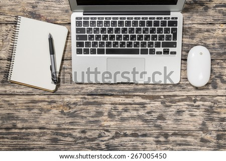 Planners. Notepad, pen, laptop and mouse on old wooden desk. View from above with copy space in vintage tone. - stock photo