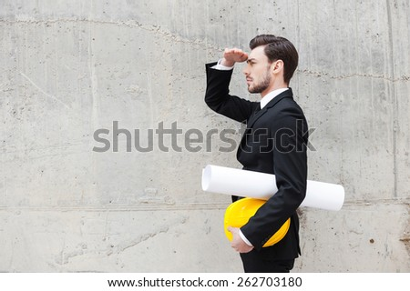 Planning a new construction. Side view of confident young man holding blueprint and hardhat and looking away while standing outdoors - stock photo