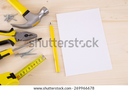 Planning a Project in Carpentry and Woodwork Industry - paper pencil and a set of tools on a wood background. - stock photo