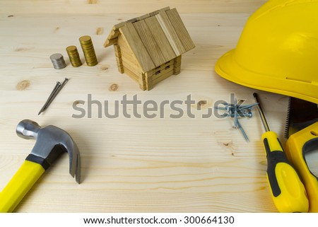 Planning a project of a home. Set of tools, money and toy home model with excessive space