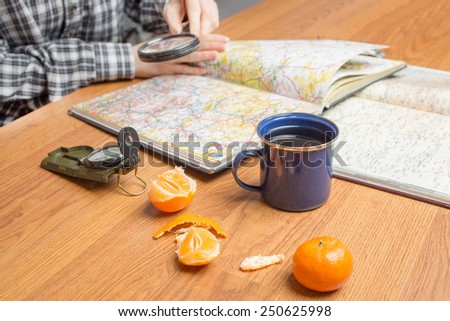 Planning a travel destination scene, focus on cup of tea - stock photo