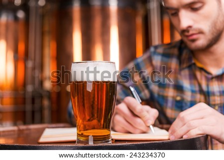 Planning his beer business. Confident young man in casual shirt writing something in his note pad while leaning at the wooden barrel with metal containers in the background   - stock photo