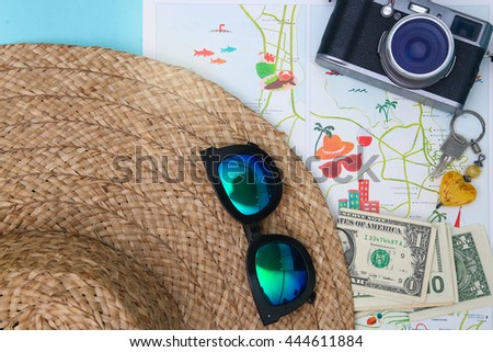 Planning next vacation - top view of straw hat, keys and some money on the map - stock photo