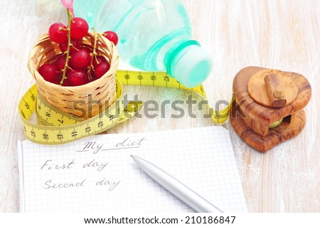 Planning of a diet. A notebook with inscription - My Diet, a measuring tape, water and red currant