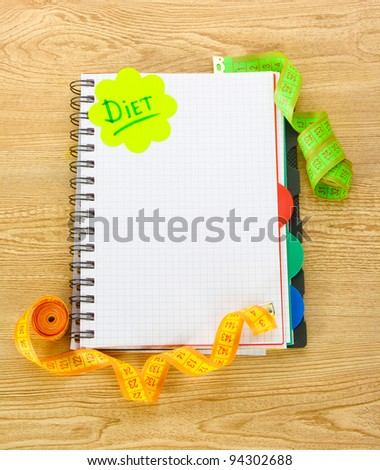 Planning of diet. Notebook measuring tapes and pen on wooden table - stock photo