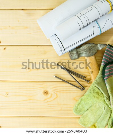 Planning of repair of the house. Repair work. Drawings for building, hammer and gloves on wooden background.