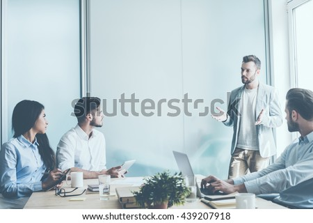 Planning strategy. Tree young business people sitting at the office desk while one man standing near them and gesturing  - stock photo
