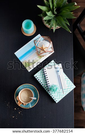 Planning summer vacation trip with cup of coffee/cappuccino/espresso. Notebooks and pen, ocean beach photo and seashells, sea scented candle on black table,with chair nearby. Overview with copy space. - stock photo