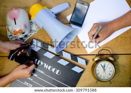 Planning to make movie with clapperboard, megaphone and piggy bank, mobile phone and alarm clock. Organize and coordinate teamwork to write scenario. - stock photo