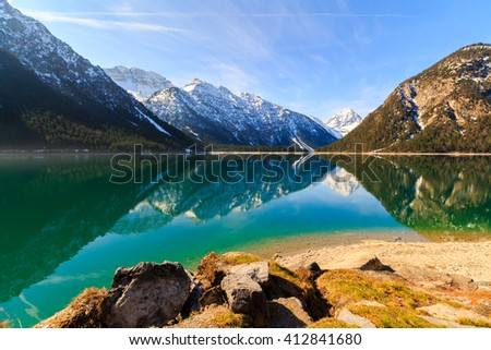 Plansee lake spring panorama with snow on mount top, Tyrol, Austria. - stock photo