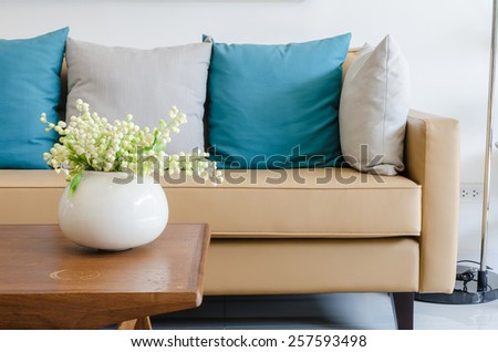plant in ceramic vase on wooden table with modern sofa at home - stock photo