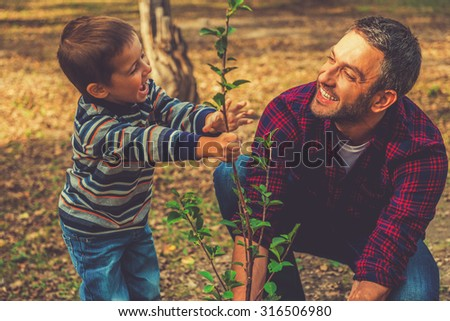 Planting a family tree. Happy young man planting a tree while his little son helping him - stock photo
