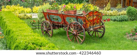 Plants and flowers in an old wood wagon in the garden. - stock photo