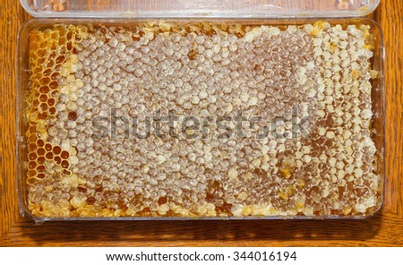 plasic box with honey in honeycomb on wooden table - stock photo
