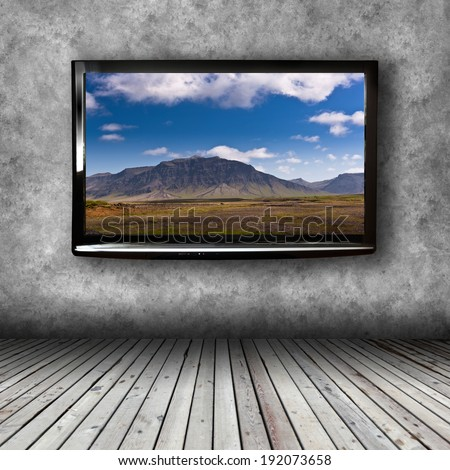 Plasma TV on the wall of the room with wooden floor - stock photo