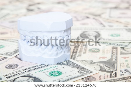 Plaster cast of teeth on dollar notes - stock photo