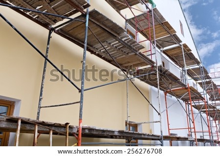 Plaster wall of building under reconstruction with scaffolding - stock photo