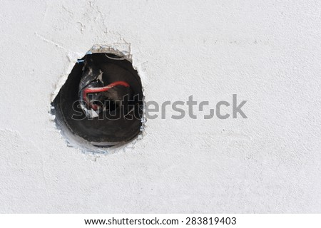 Plastered wall with exposed wires in wall socket