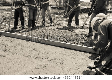 plasterer concrete cement work. leveling concrete slab floor work step of the building construction by worker.sepia color tone for old feel - stock photo