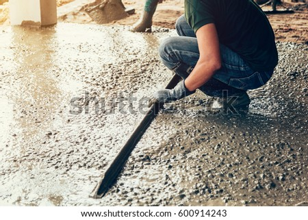 plasterer concrete worker at floor of house construction