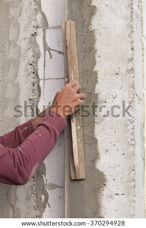 plasterer concrete worker at wall of house construction at construction site - stock photo