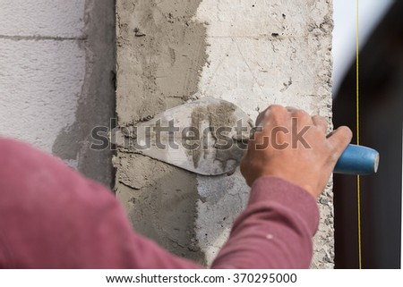 plasterer concrete worker at wall of house construction at construction site