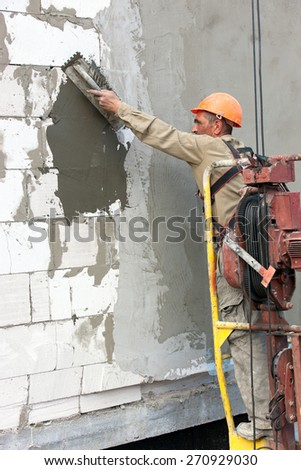 Plasterer crafts man builder worker plastering multi storey building wall of bricks or concrete blocks during finishing construction works - stock photo