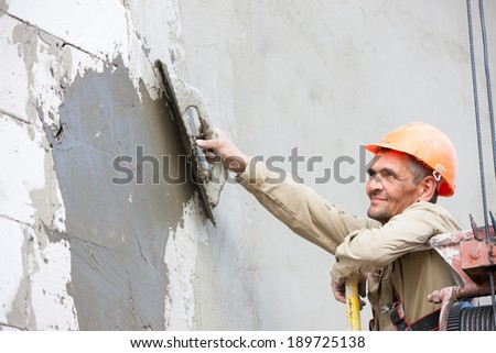 Plasterer crafts man worker plastering multi storey building wall of bricks or concrete blocks during finishing construction works - stock photo