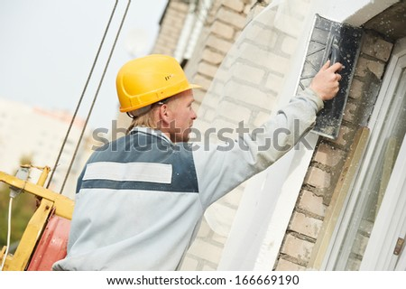 Plasterer facade builder worker with scratching tool at thermal insulation works