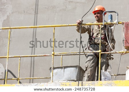 Plasterer Man Worker lifting in Building hoist Construction Elevator Cradle Lifter Gondola Suspended Platform - stock photo