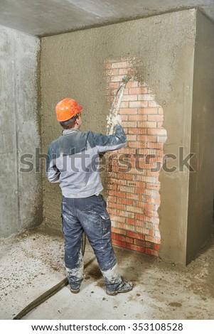 Plasterer operating sprayer equipment machine for spraying thin-layer putty plaster finishing on brick wall  - stock photo