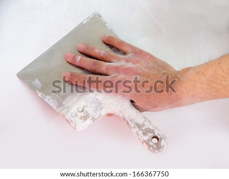 Plastering man hand with plaste and plaster spatula trowel in wall - stock photo