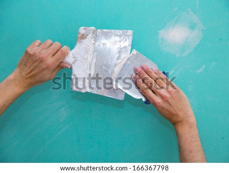 Plastering man hands with plaste on drywall plasterboard hydrophobic construction - stock photo